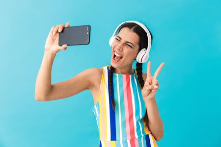 Image of brunette beautiful woman wearing headphones winking while using cellphone isolated over blue wall Stock Photo - 129823722
