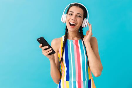 Image of brunette pleased woman smiling while using headphones and cellphone isolated over blue wall Stock Photo - 129823723