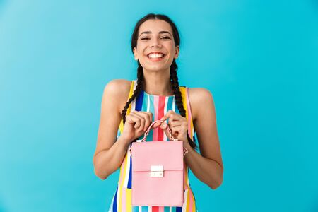 Image of pleased caucasian woman with pigtails holding pink bag and smiling isolated over blue wall