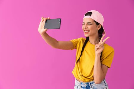Image of attractive woman wearing cap showing peace sign and taking selfie photo on cellphone isolated over pink wall Stock Photo - 129823690