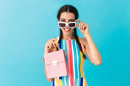Image of brunette smiling woman wearing sunglasses looking at camera while holding pink bag isolated over blue wall Stock Photo - 129823698