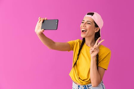 Image of joyous woman wearing cap showing peace sign and taking selfie photo on cellphone isolated over pink wall Stock Photo - 129823700