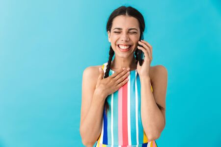 Image of amazed beautiful woman with eyes closed talking on cellphone and laughing isolated over blue wall