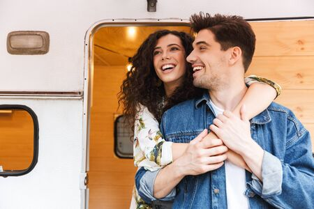 Cheerful young couple talking while standing at the campvan, hugging Stock Photo