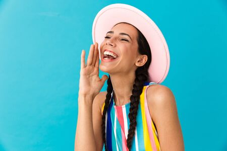 Image closeup of laughing caucasian woman wearing hat calling and smiling isolated over blue wall Stock Photo - 129823705