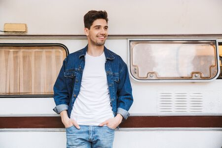 Portrait of happy man wearing denim jacket smiling with his hands in pockets while standing near house on wheels outdoors