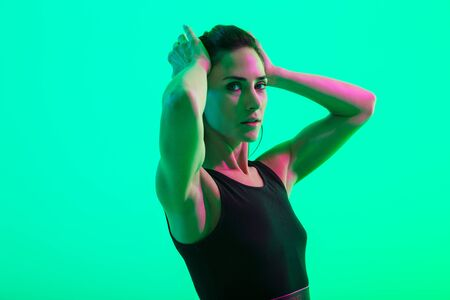 Beautiful young fitness girl standing isolated over green neon background, doing stretching exercises Stock fotó