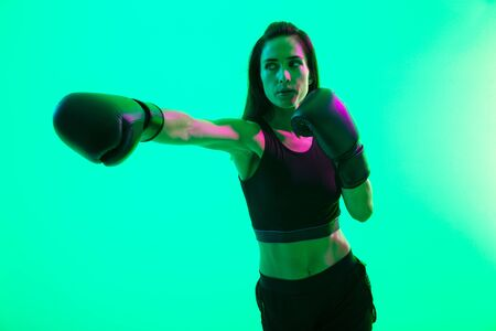 Beautiful confident young fitness girl standing isolated over green neon background, boxing