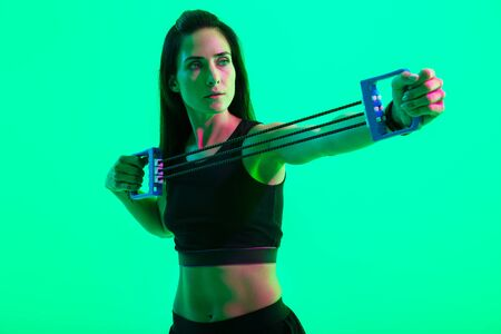Beautiful confident young fitness girl sitting on a fitness mat isolated over green neon background, working out with an expander