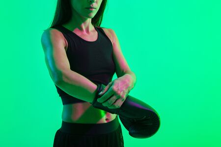 Cropped photo of a young strong sports woman boxer posing isolated over blue wall background with neon bright lights wearing gloves.