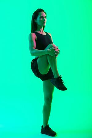 Full length of a beautiful young fitness girl wearing wireless earphones isolated over green neon background, doing stretching exercises