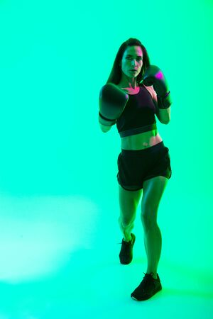 Full length of a beautiful confident young fitness girl standing isolated over green neon background, boxing Stock fotó