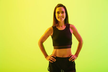 Beautiful smiling young fitness girl standing isolated over blue background, holding hands on hips
