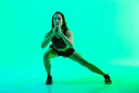 Full length of a beautiful young fitness girl working out isolated over green background, doing lunges
