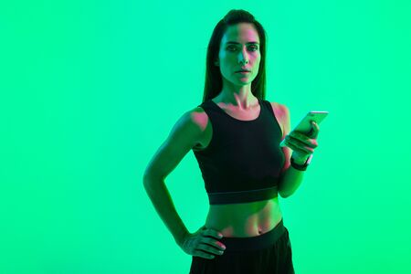 Photo of a serious strong sports woman posing isolated over blue wall background with neon bright lights using mobile phone chatting. Stock fotó