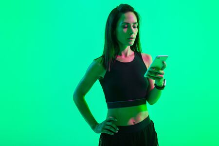 Portrait of a beautiful concentrated strong sports woman posing isolated over blue wall background with neon bright lights using mobile phone chatting.