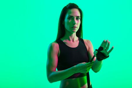 Beautiful young fitness girl standing isolated over green neon background