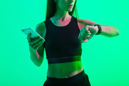 Cropped photo of a young strong sports woman isolated over blue wall background with neon bright lights using mobile phone looking at watch clock. Imagens