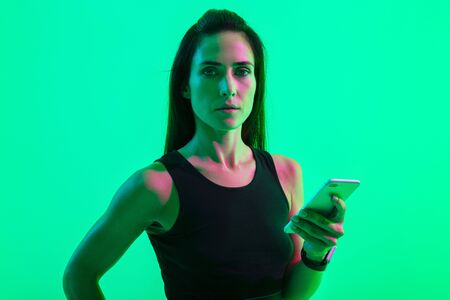 Photo of a young concentrated strong sports woman posing isolated over blue wall background with neon bright lights using mobile phone chatting.