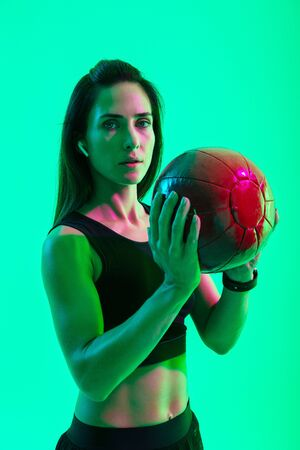 Beautiful confident young fitness girl standing isolated over green neon background, wearing wireless earphones, working out with a medicine ball Фото со стока