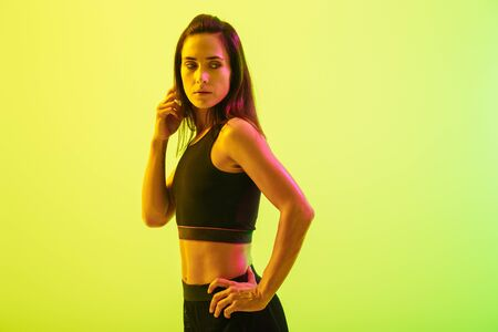Beautiful young fitness girl standing isolated over blue background, looking away Stock fotó