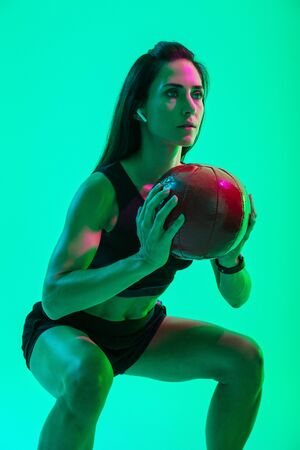 Beautiful confident young fitness girl standing isolated over green neon background, wearing wireless earphones, working out with a medicine ball, squatting