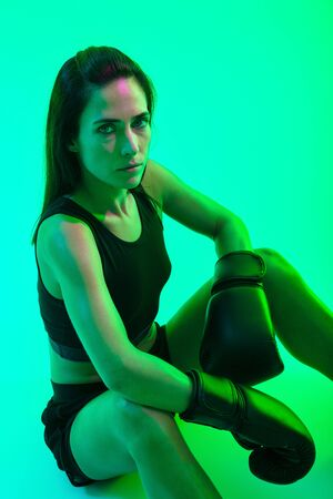 Beautiful confident young fitness girl wearing boxing gloves sitting isolated over green neon background, looking up