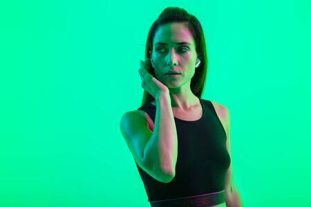 Beautiful young fitness girl standing isolated over green neon background, wearing wireless earphones