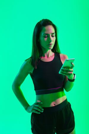 Image of a young serious strong sports woman posing isolated over blue wall background with neon bright lights using mobile phone chatting. Stock fotó