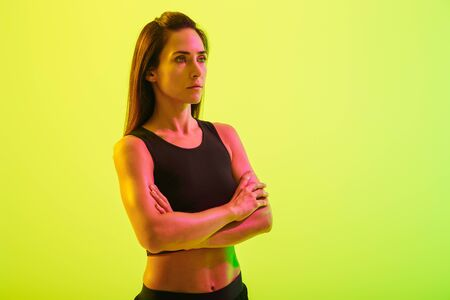 Beautiful young fitness girl standing isolated over blue background, arms folded