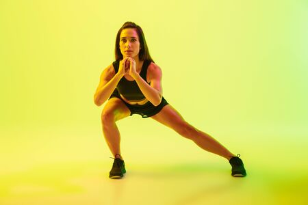 Full length of a beautiful young fitness girl working out isolated over yellow background, doing lunges
