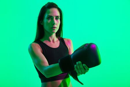 Beautiful confident young fitness girl standing isolated over green neon background, taking off a boxing glove
