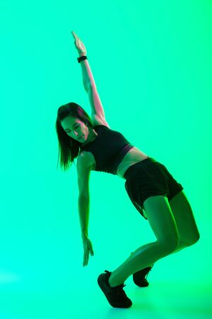 Full length of a beautiful young fitness girl standing isolated over green neon background, doing stretching exercises