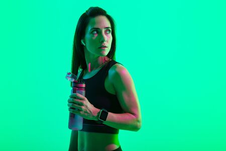 Beautiful confident young fitness girl standing isolated over green neon background, wearing wireless earphones, holding water bottle after workout