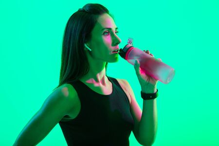 Beautiful confident young fitness girl standing isolated over green neon background, wearing wireless earphones, drinking water from a bottle after workout
