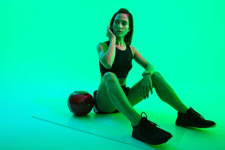 Beautiful confident young fitness girl sitting on a fitness mat isolated over green neon background, wearing wireless earphones, working out with a medicine ball