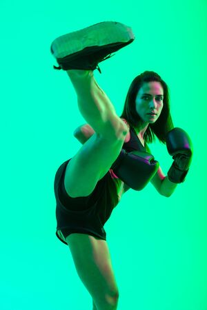 Full length of a beautiful confident young fitness girl standing isolated over green neon background, kicking with her leg while boxing