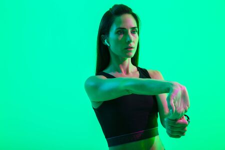 Beautiful young fitness girl wearing wireless earphones isolated over green neon background, doing stretching exercises Stock fotó