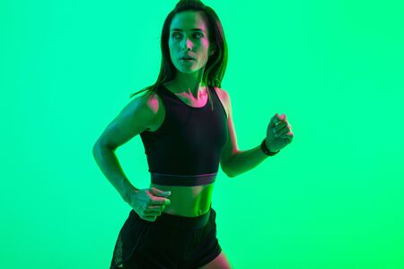 Image of a young serious strong sports woman isolated over blue wall background with neon bright lights running.