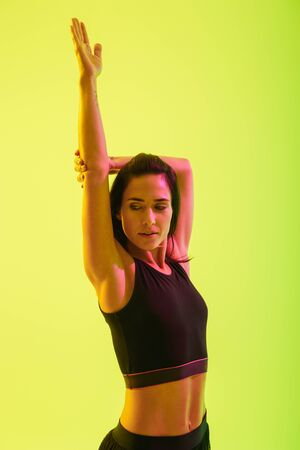 Beautiful young fitness girl standing isolated over blue background, doing stretching exercises