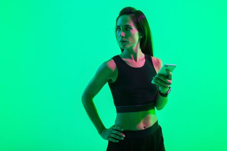 Image of a young serious strong sports woman posing isolated over blue wall background with neon bright lights using mobile phone chatting. Stock Photo