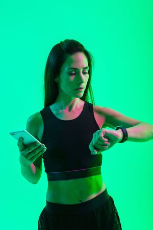 Photo of a young gorgeous concentrated strong sports woman isolated over blue wall background with neon bright lights using mobile phone looking at watch clock. Imagens