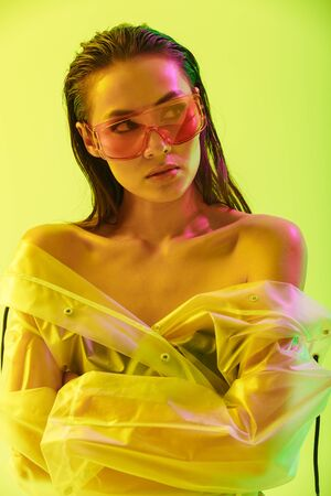 Fashion portrait of an attractive young asian woman with long wet hair standing isolated over yellow background, posing in transparent raincoat and sunglasses, looking away
