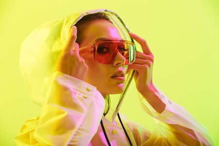 Fashion close up portrait of an attractive young asian woman with long wet hair standing isolated over yellow background, posing in transparent raincoat and sunglasses Фото со стока