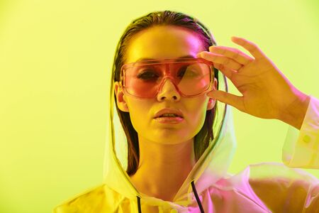 Fashion portrait of an attractive young asian woman with long wet hair standing isolated over yellow background, posing in transparent raincoat and sunglasses
