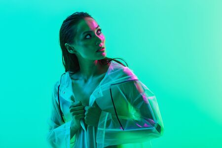 Picture of naked amazing pretty serious woman posing isolated over blue wall background with neon bright lights dressed in raincoat looking at copyspace.