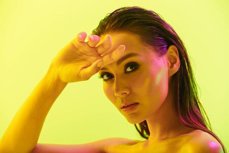 Image of a gorgeous amazing young woman posing isolated over yellow wall background with neon bright lights.