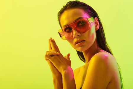 Picture of a beautiful amazing young woman posing isolated over yellow wall background with neon bright lights wearing fashion sunglasses showing gun gesture. Stock fotó