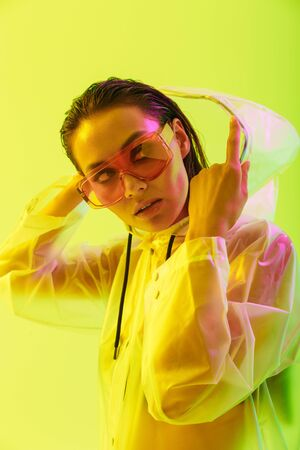 Fashion portrait of an attractive young asian woman with long wet hair standing isolated over yellow background, posing in transparent raincoat and sunglasses Standard-Bild - 130006752