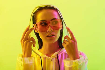 Picture of attractive amazing young woman posing isolated over yellow wall background with neon bright lights wearing fashion sunglasses dressed in raincoat.
